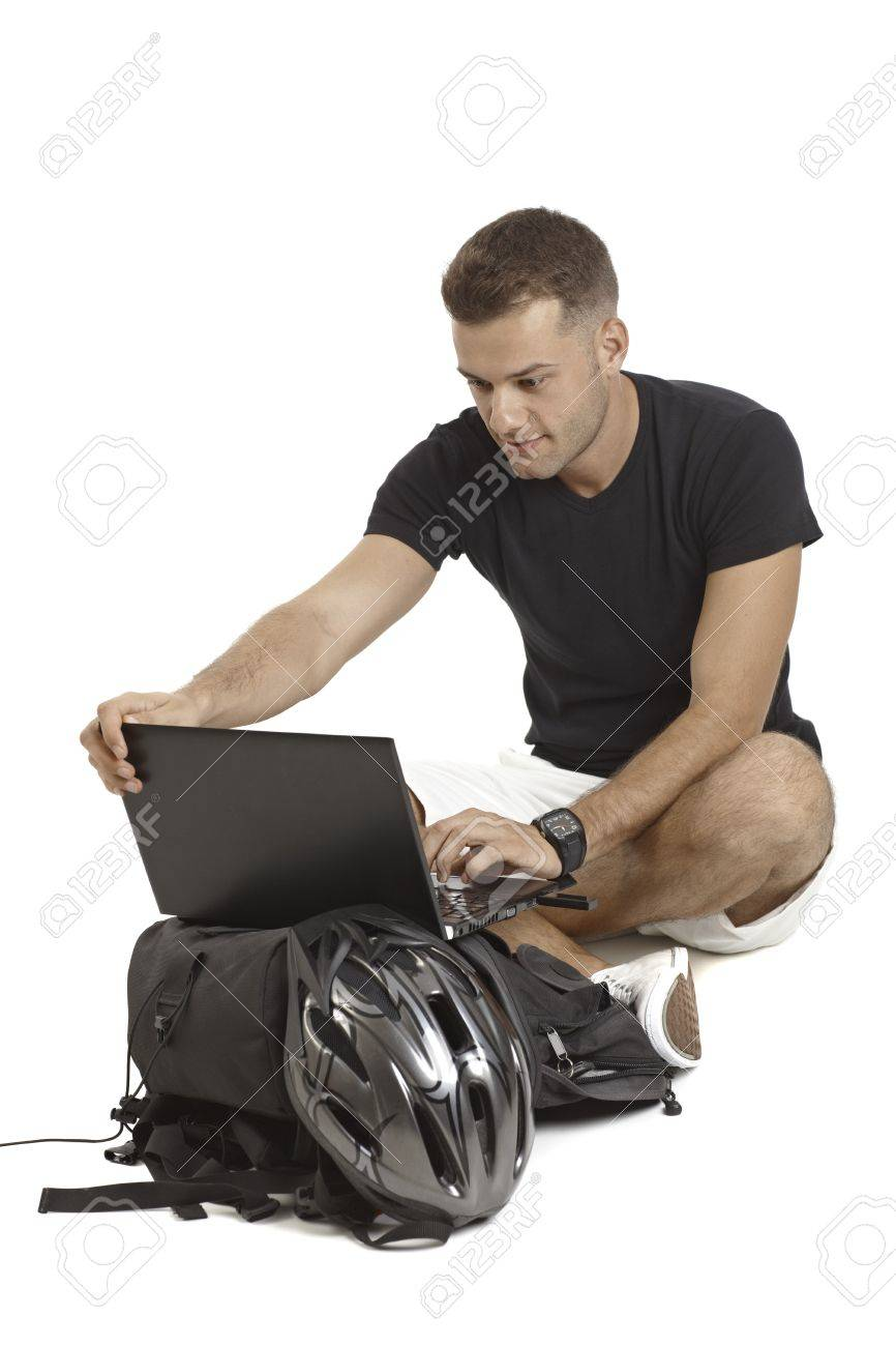Casual young man using laptop computer, having backpack and helmet, sitting in tailor seat. Stock Photo - 15965948