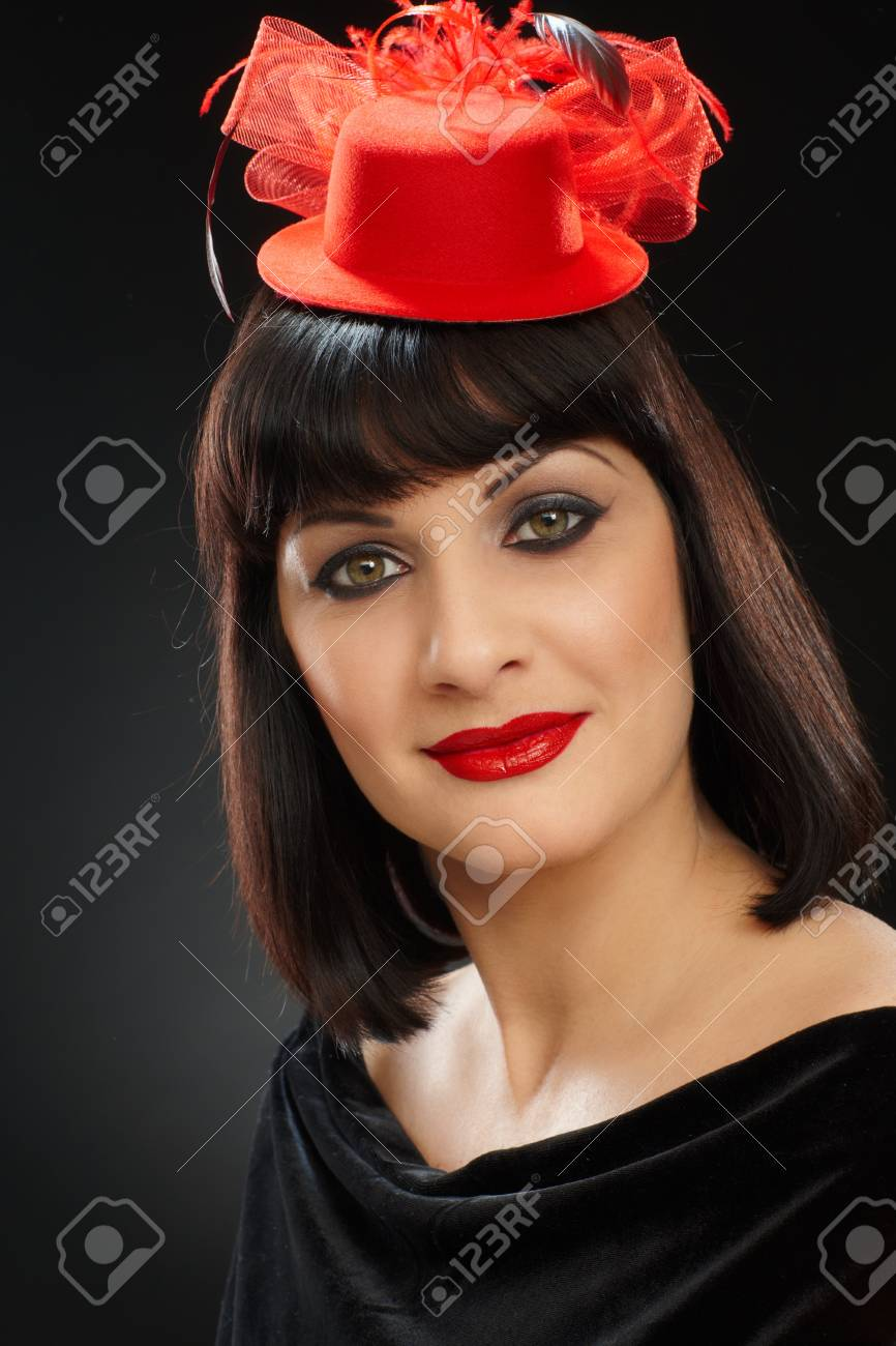 Studio portrait of young woman in red hat looking at camera, smiling. Stock Photo - 16761856
