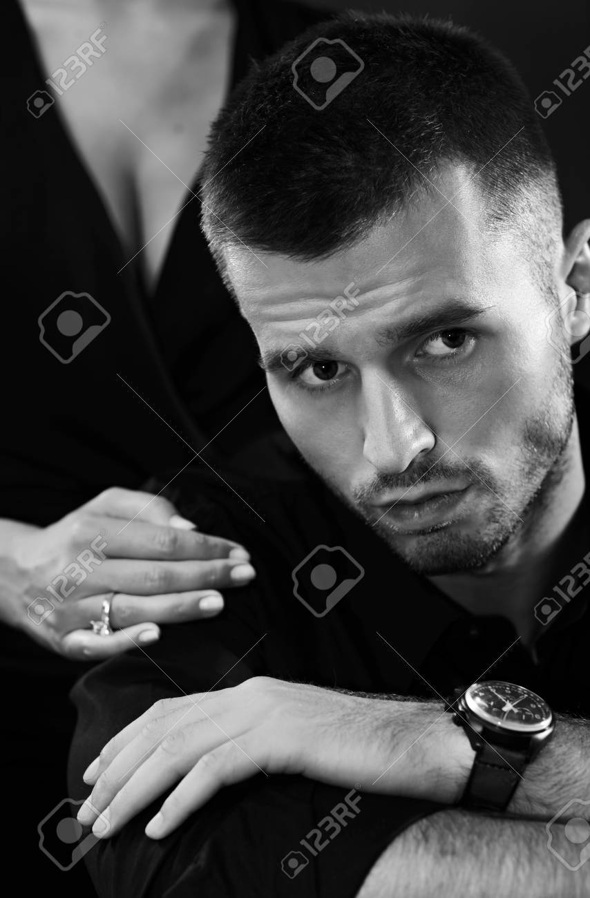 Black-and-white portrait of serious young man, woman standing behind. Stock Photo - 16859290