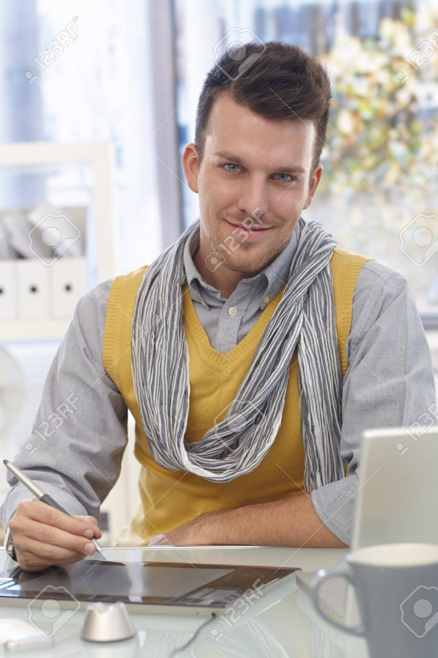 Handsome young man sitting at desk, using drawing pad, smiling, looking at camera. Stock Photo - 16764847