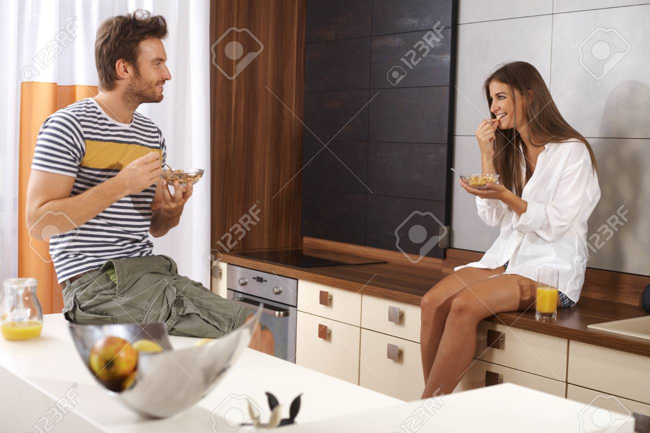 Young loving couple having breakfast in the kitchen, smiling happy Stock Photo - 17098465