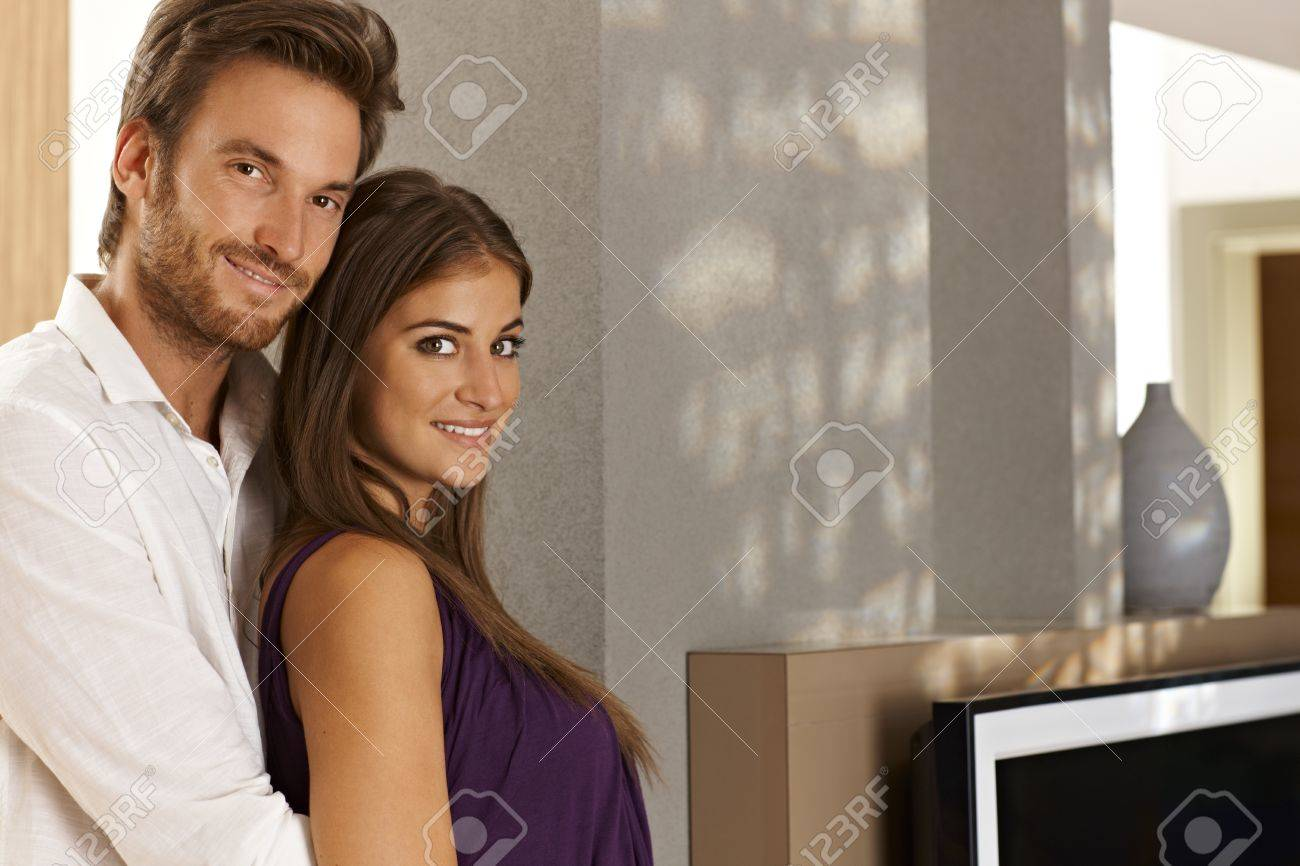 Portrait of beautiful young loving couple embracing at home in living room. Stock Photo - 17098457