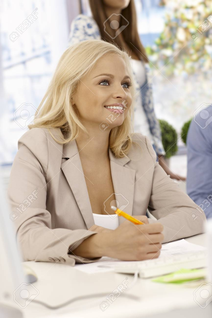 Portrait of attractive young businesswoman sitting at desk, writing notes, smiling. Stock Photo - 17132686