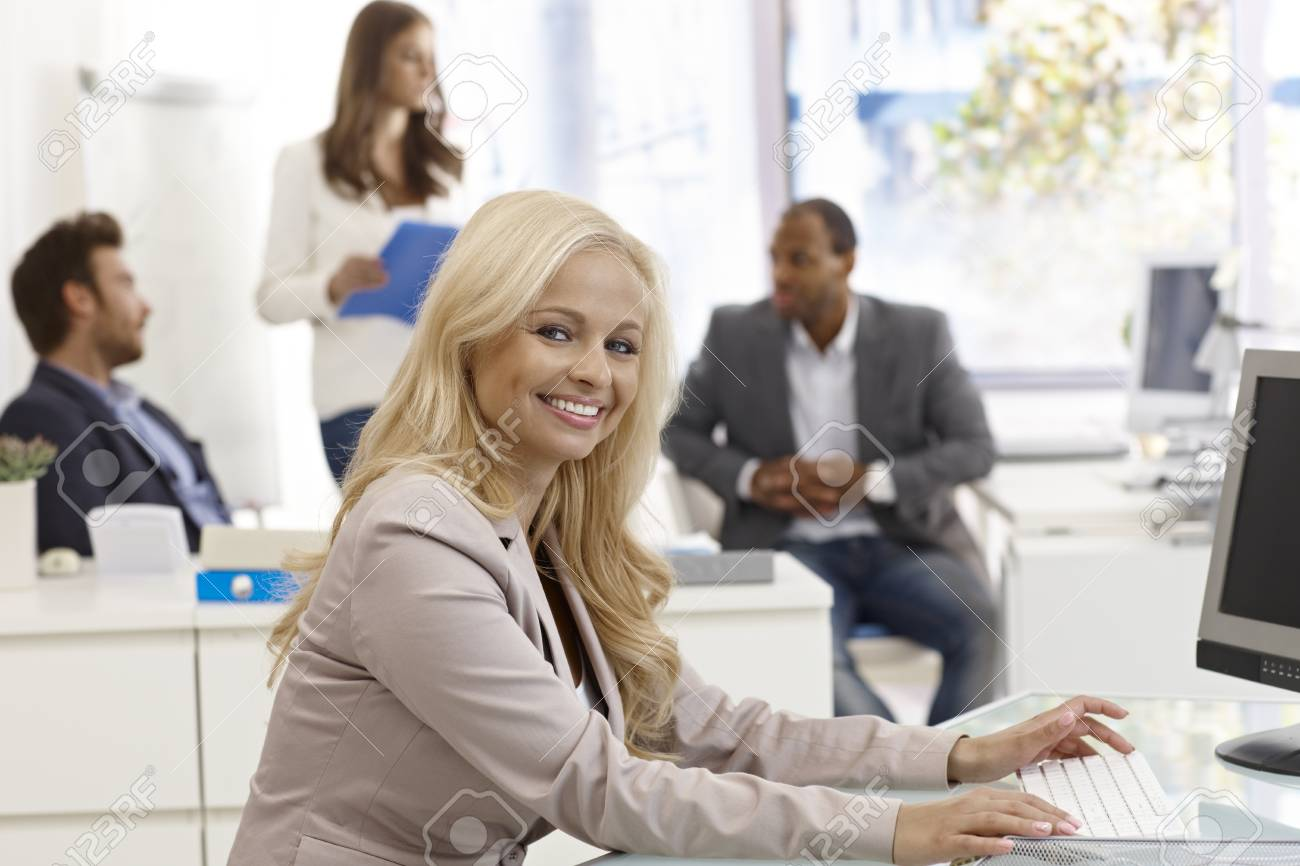 Portrait of beautiful young blonde businesswoman sitting at desk, working with computer, smiling happy. Stock Photo - 17134031