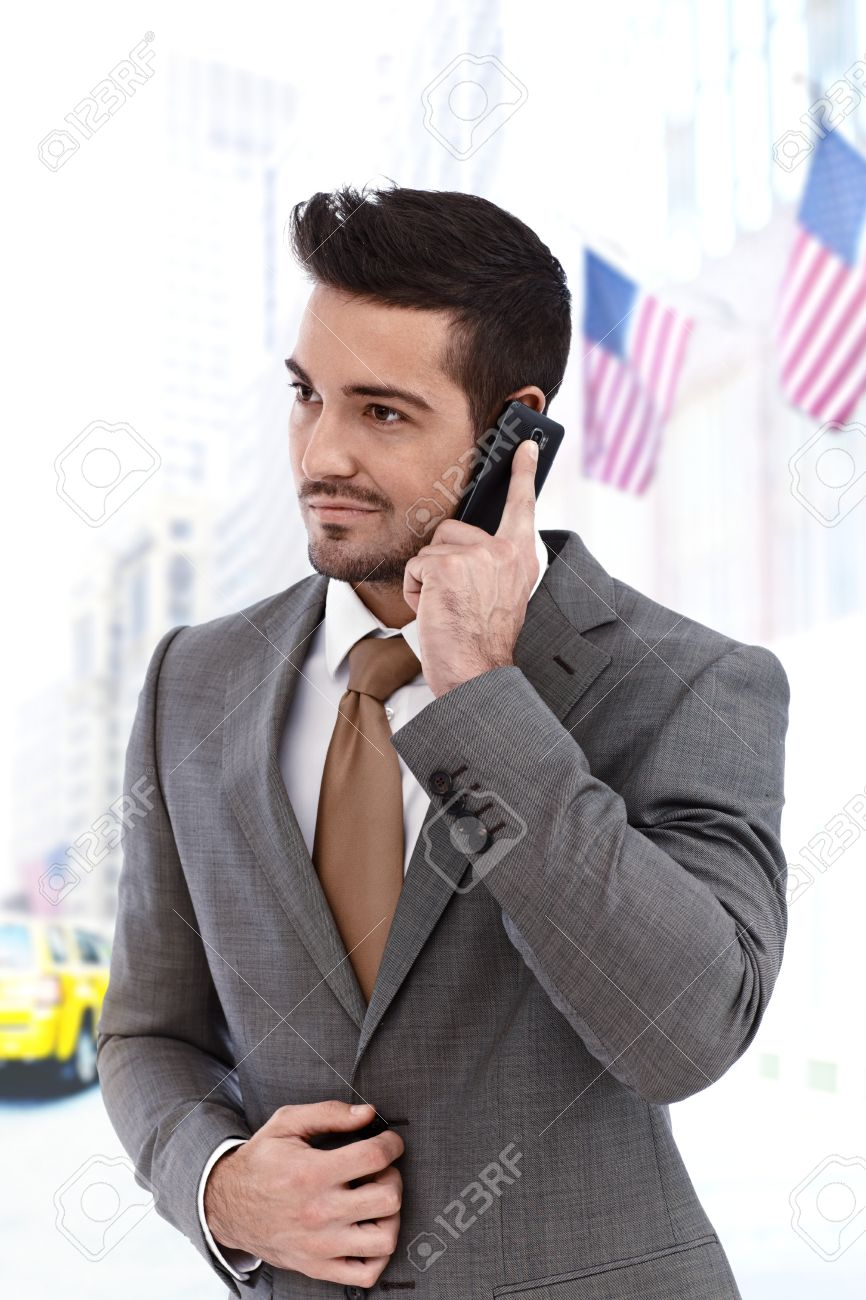 Young businessman on the phone walking outdoors, american flags in background Stock Photo - 17193927