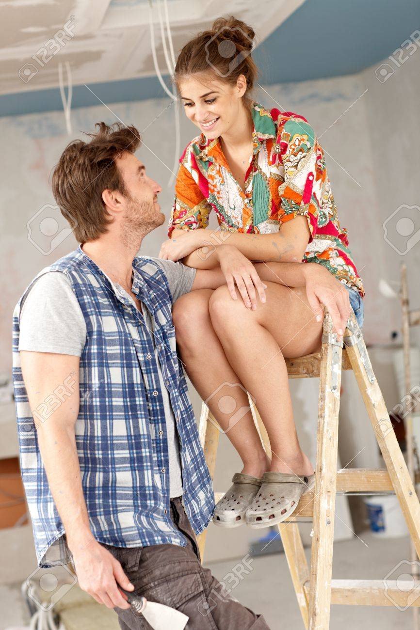 Young couple renewing home, woman sitting on top of ladder, smiling   65533; Stock Photo - 17423450