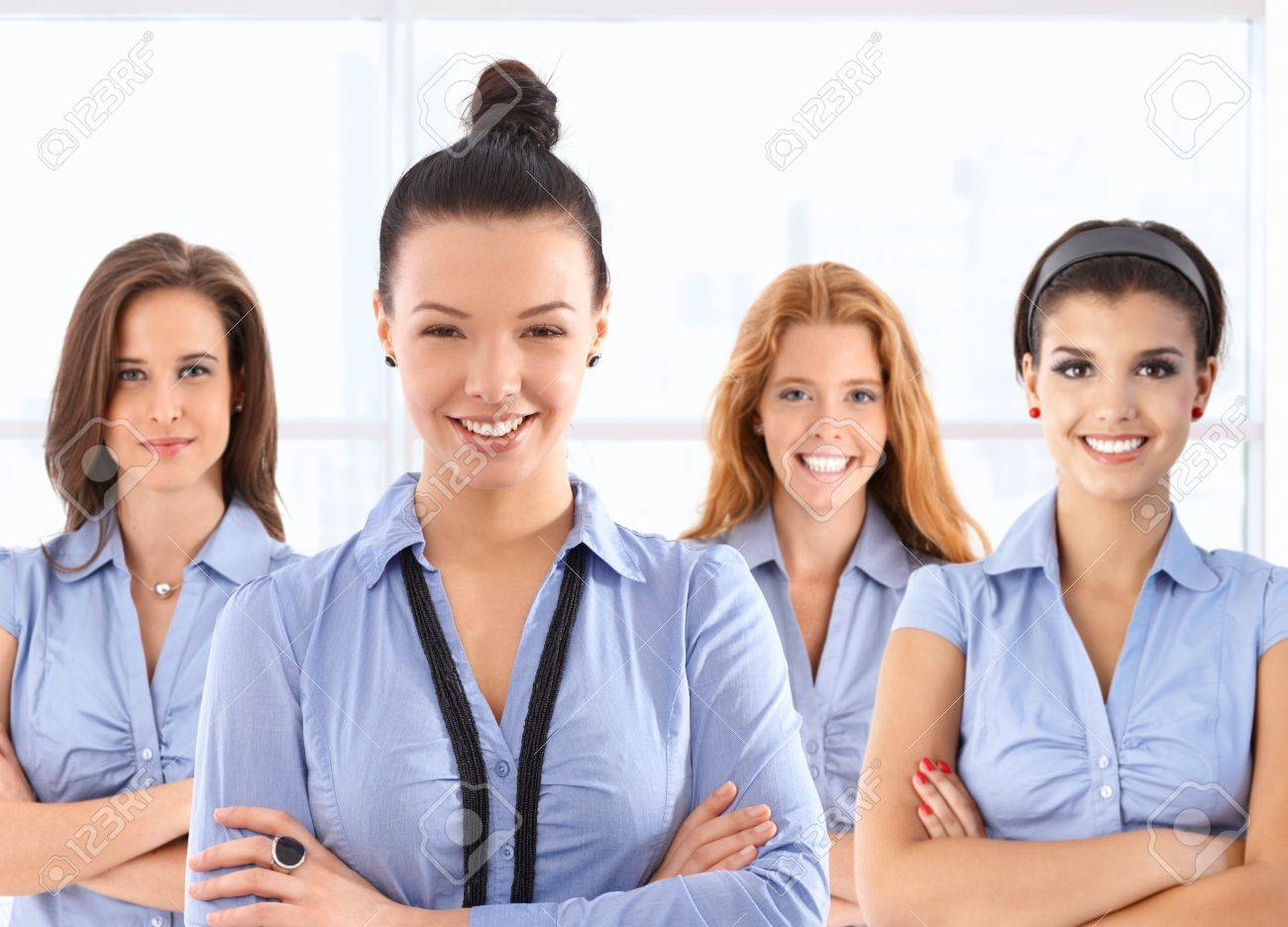 Team portrait of attractive young female front office workers in blue uniform, looking at camera, smiling. Stock Photo - 17638919