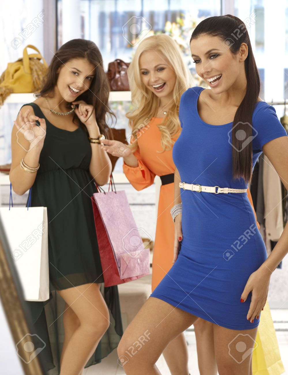 Happy Girls Shopping Together, One Trying On Blue Mini Dress ...
