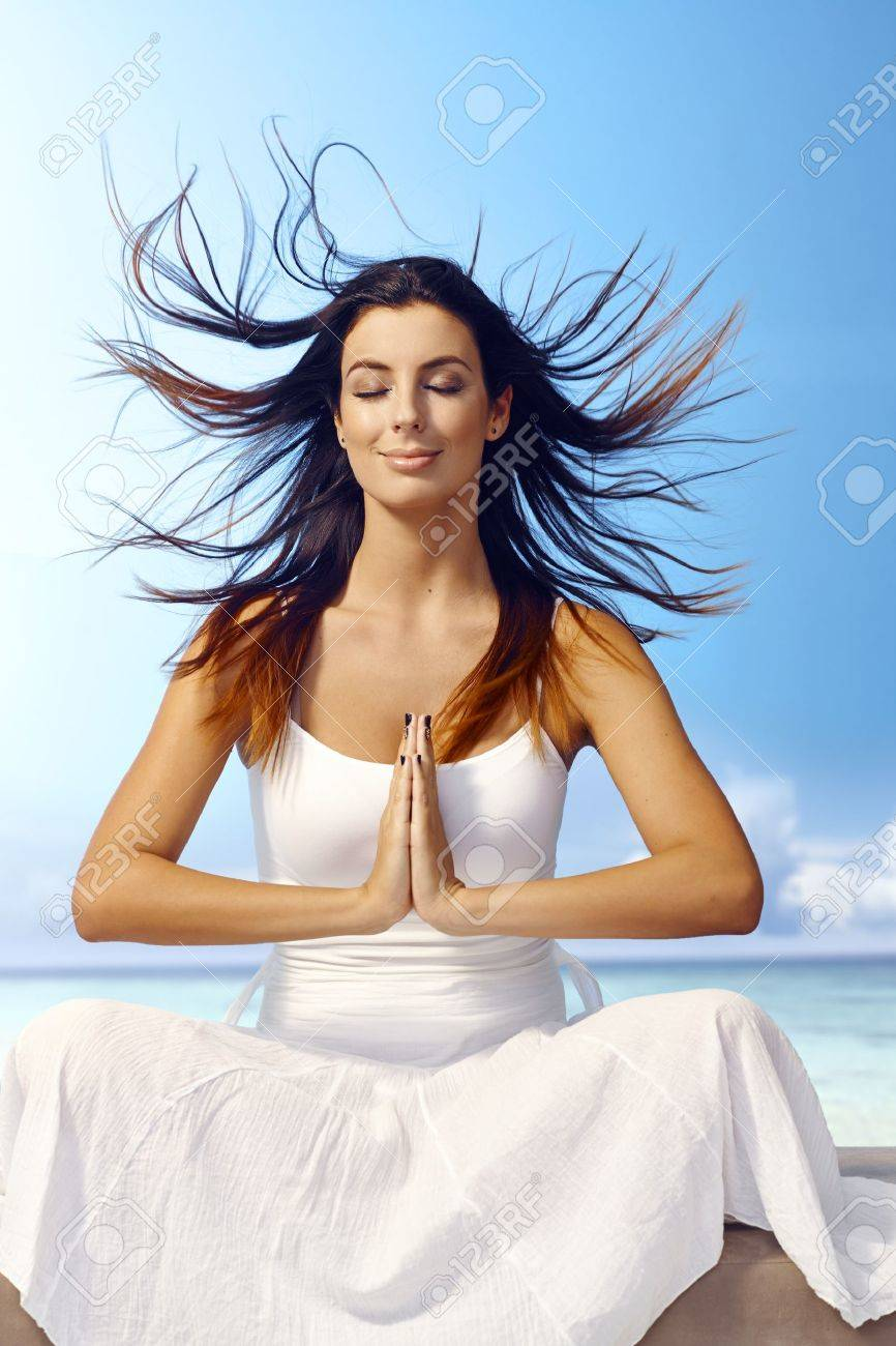 Attractive young woman meditating on the beach eyes closed, wind blowing hair, smiling, sitting in prayer position. Stock Photo - 19365810