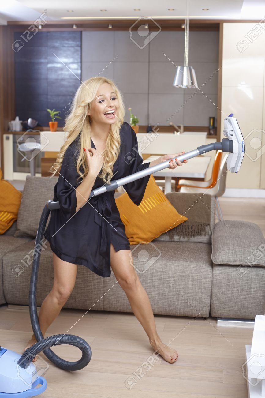 Happy Blonde Frau Mit Staubsauger Als Gitarre Spass Zu Hause Im Wohnzimmer Lachen