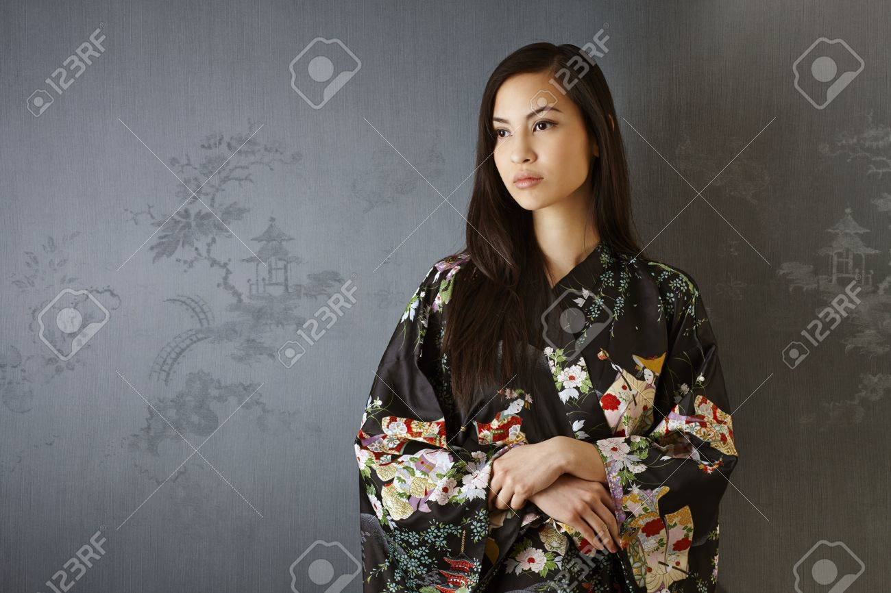 Portrait of Japanese woman in traditional kimono standing by grey wall, looking away. Stock Photo - 22070824