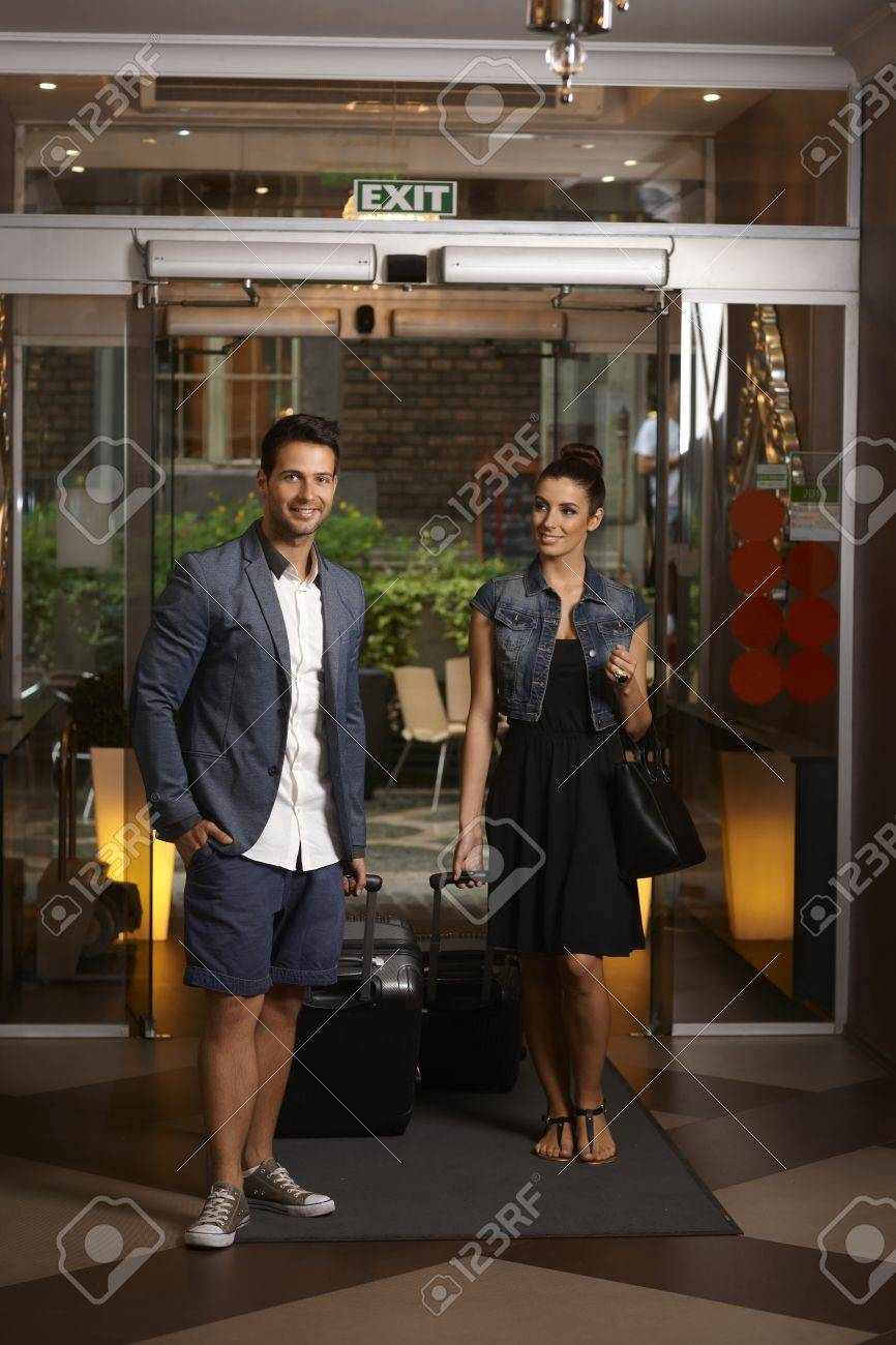 Young couple arriving at hotel with suitcases, smiling. Stock Photo - 22307923