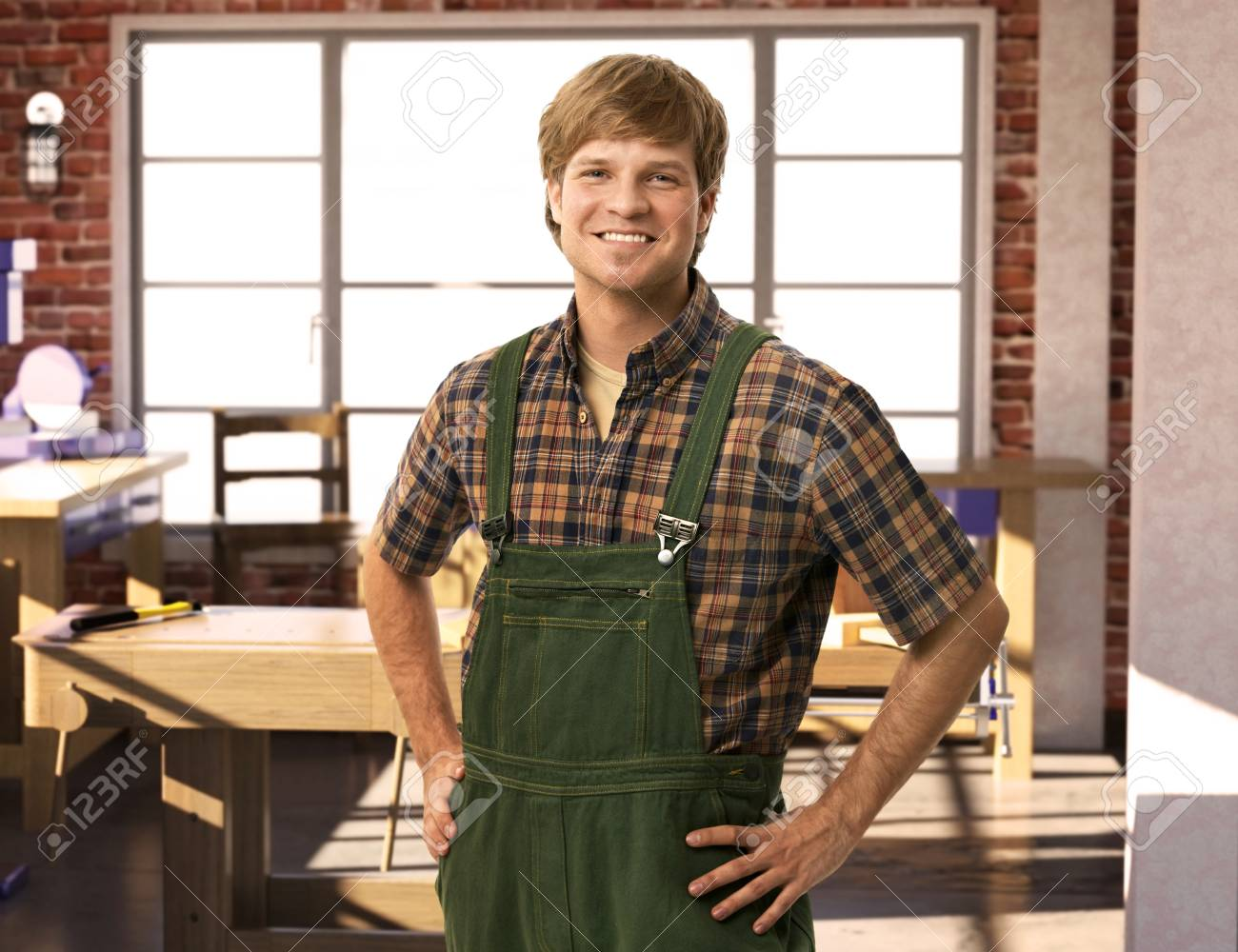 Happy young handyman carpenter in workshop, smiling. Stock Photo - 23206615