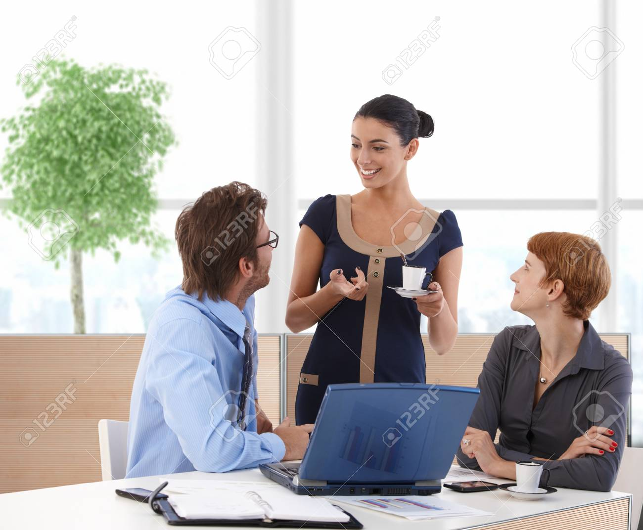 Businesspeople talking in business hall sitting at desk using laptop. Stock Photo - 23413616
