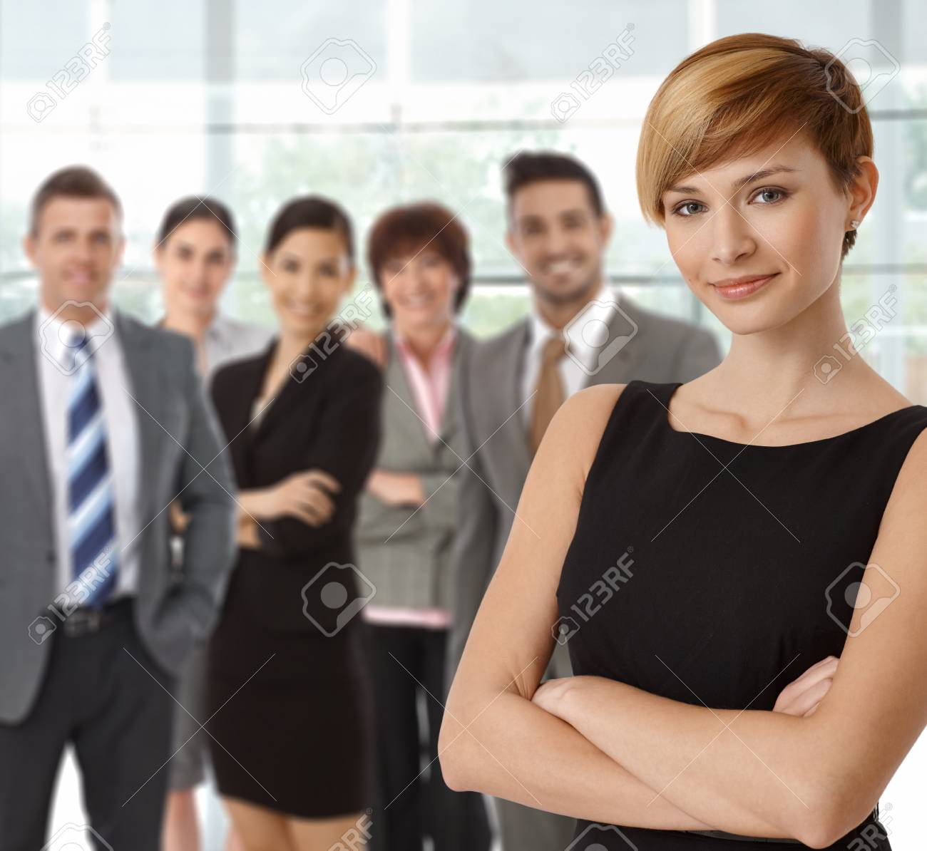 Beautiful young businesswoman smiling with business team in background. Stock Photo - 23527926