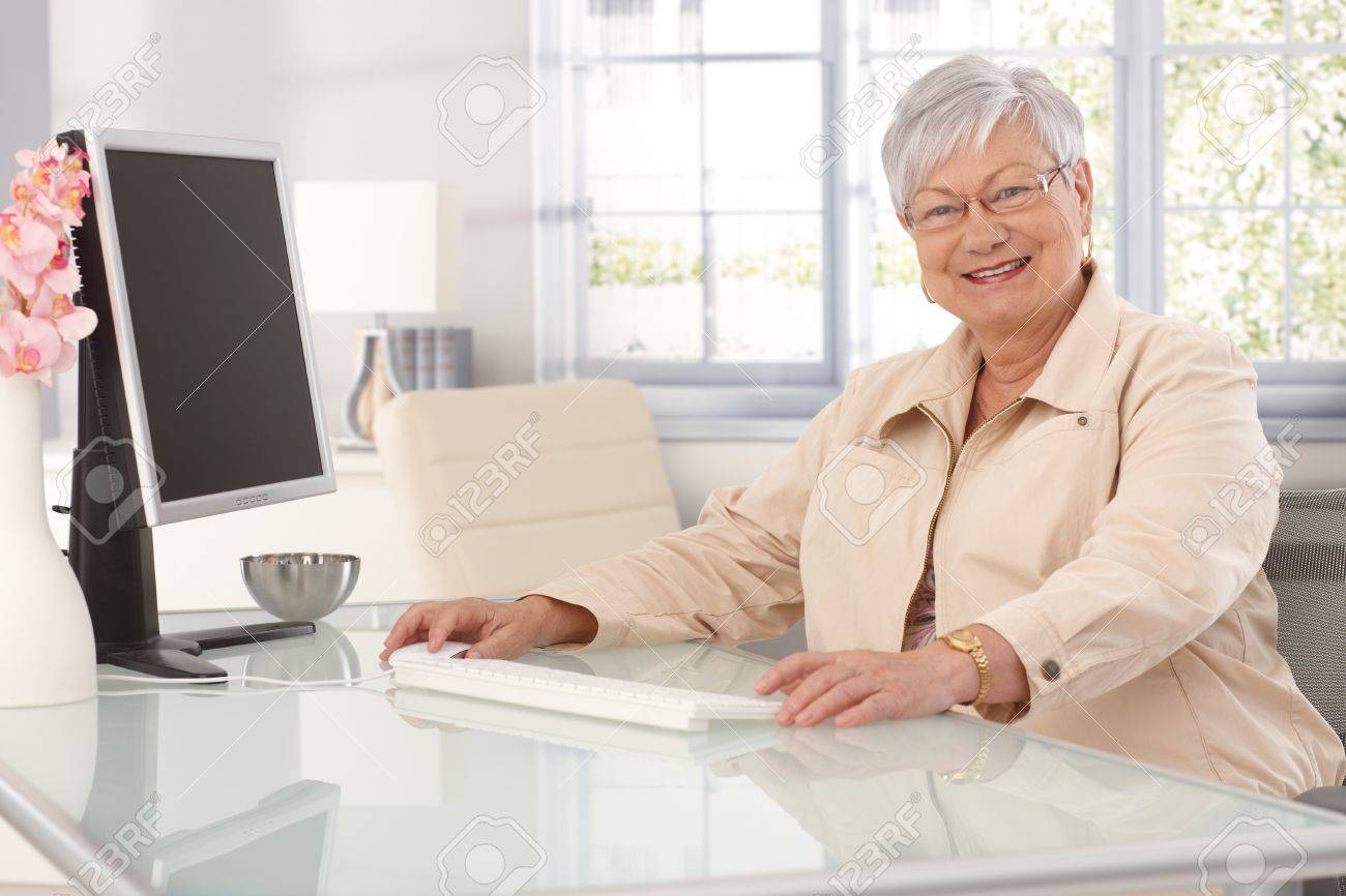 Lady Sitting at Computer Happy Elderly Lady Sitting at