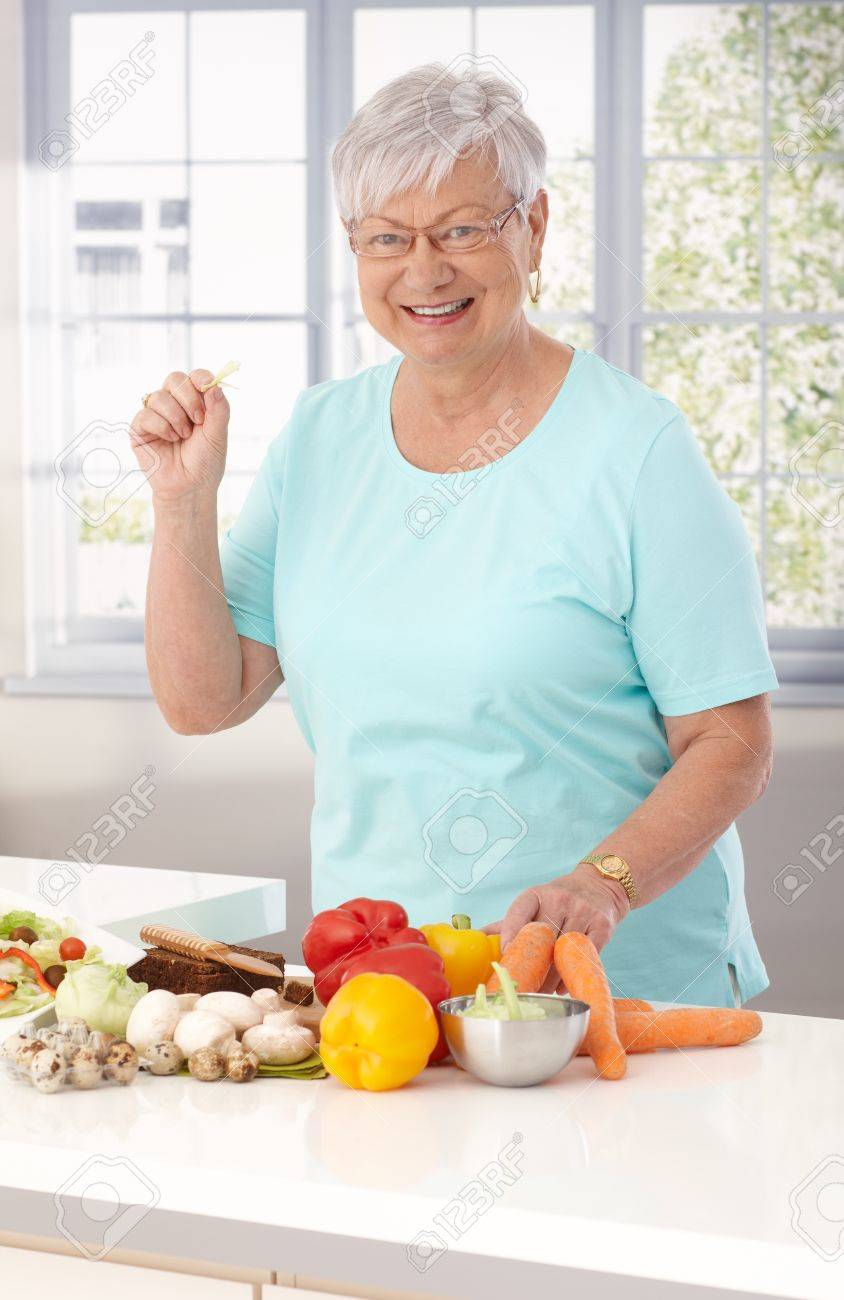Elderly Lady Preparing Healthy Food In Kitchen, Using Vegetables ...