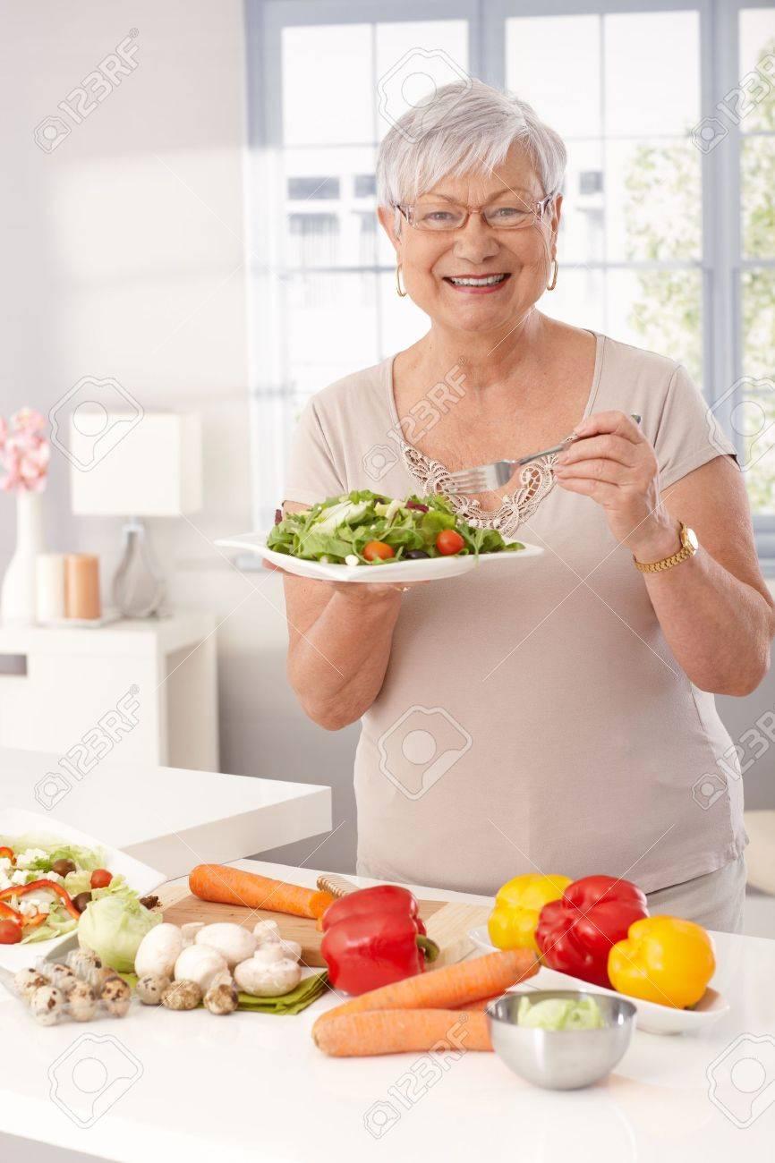 Moderne oma eten van verse groene salade en groenten in de keuken ...