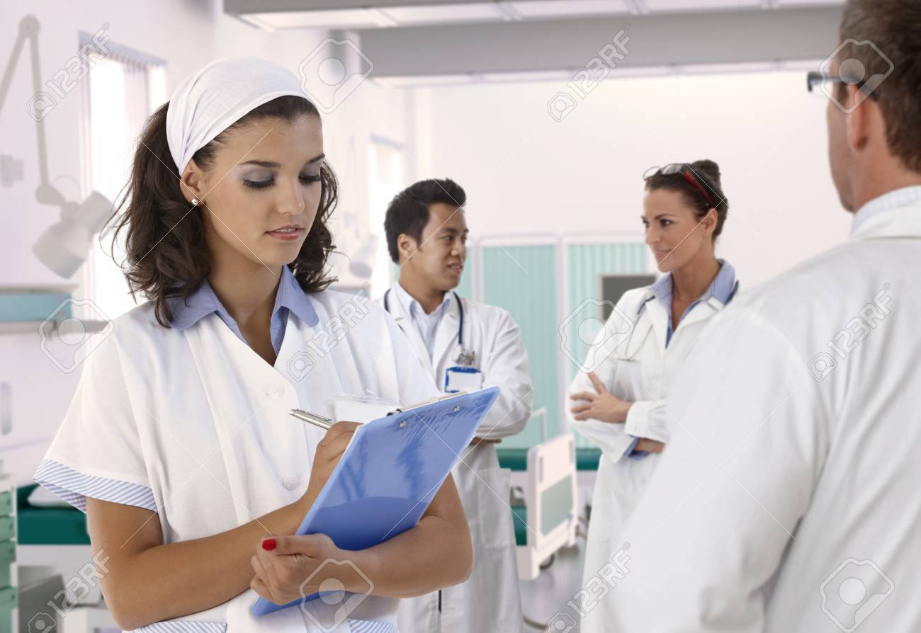 Nurse writing on clipboard at hospital room, doctors consulting. Stock Photo - 26368750