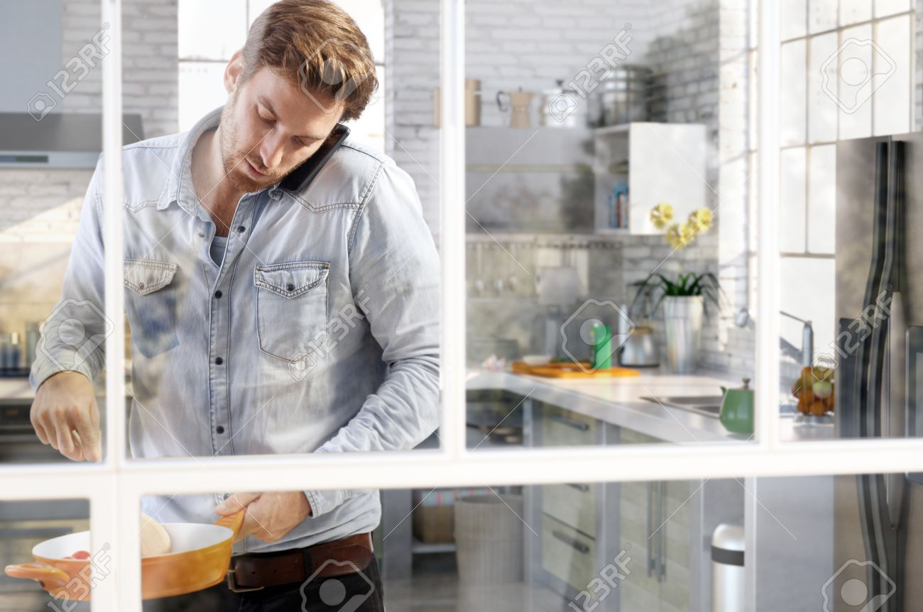 Casual Young Man Cooking In Kitchen Chatting On Phone, Through ...