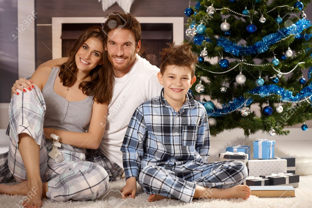 Happy Young Family Sitting On Floor At Christmas Morning In ...