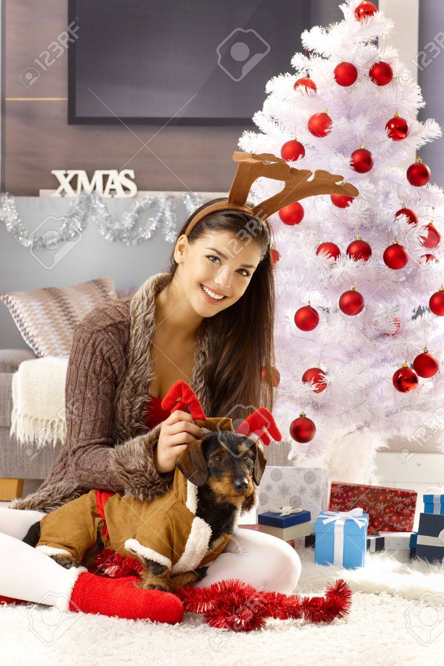young woman celebrating christmas with dog smiling having fun