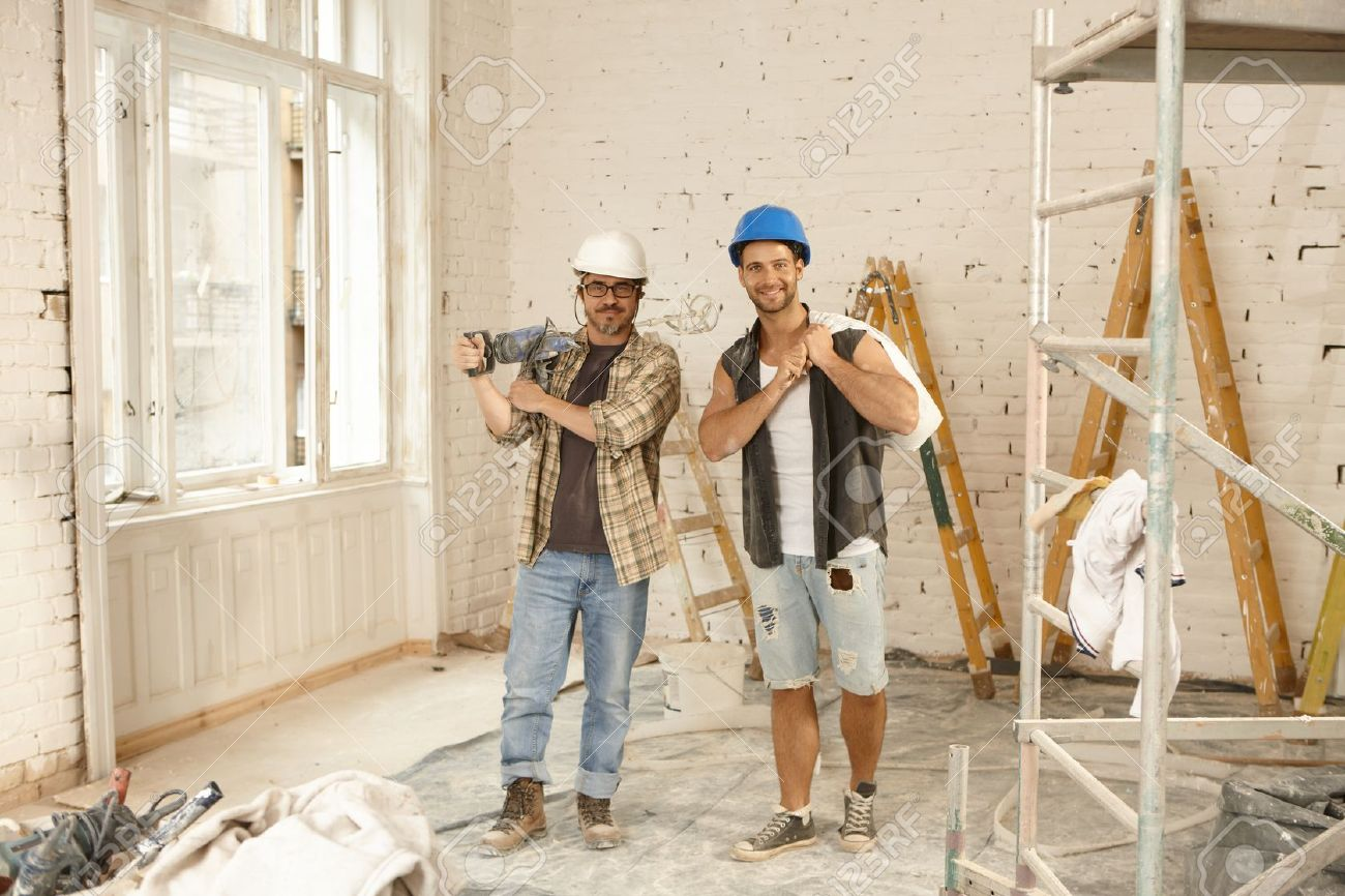 Happy workers standing at renovation site, smiling, looking at camera. - 50901990
