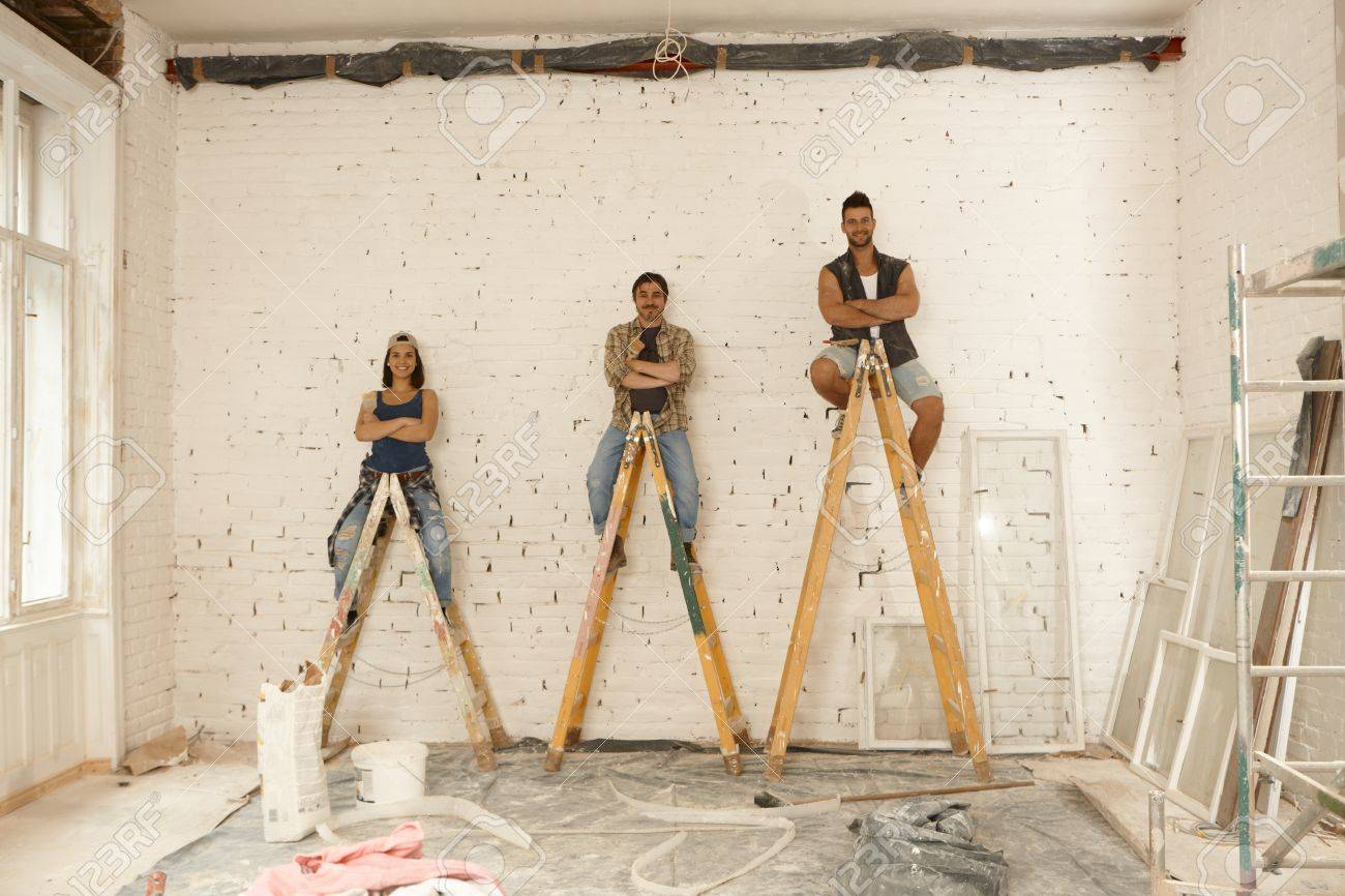 Team photo of workers renovating house, sitting on top of ladder, smiling  arms crossed
