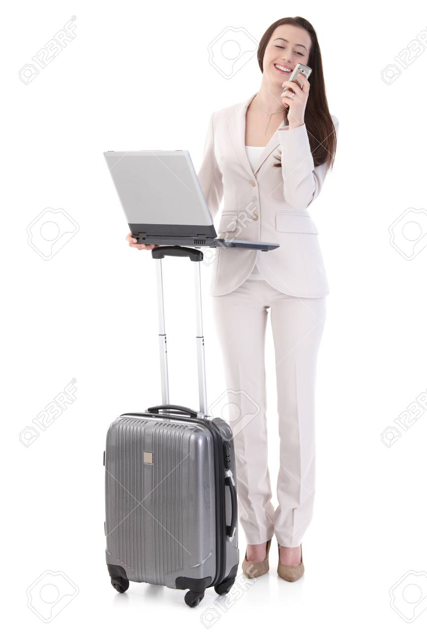 Happy young businesswoman standing in business suit with suitcase, using laptop computer, talking on mobile phone, looking away, smiling. Isolated on white. - 125785047
