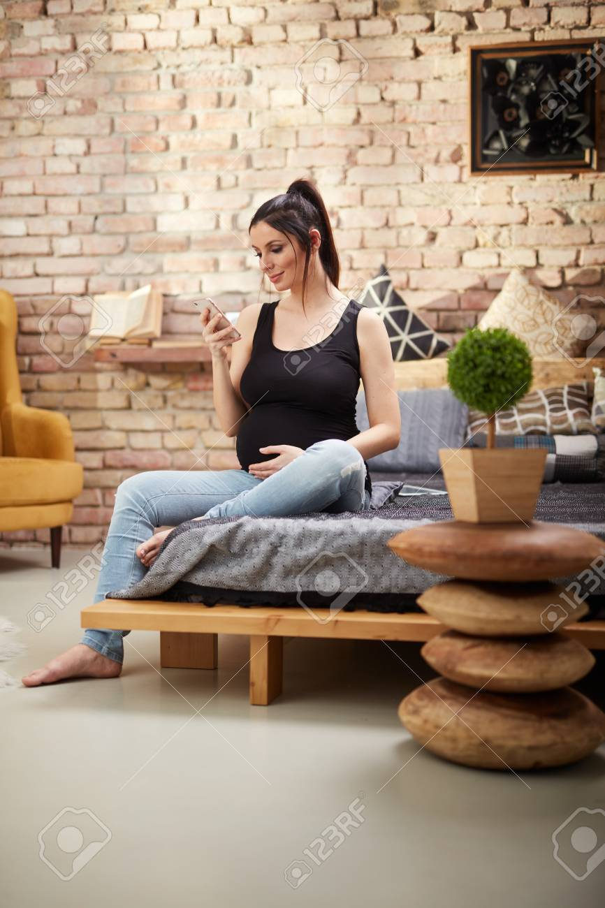 Happy pregnant woman sitting at home smiling, relaxing using mobile phone. - 125784998