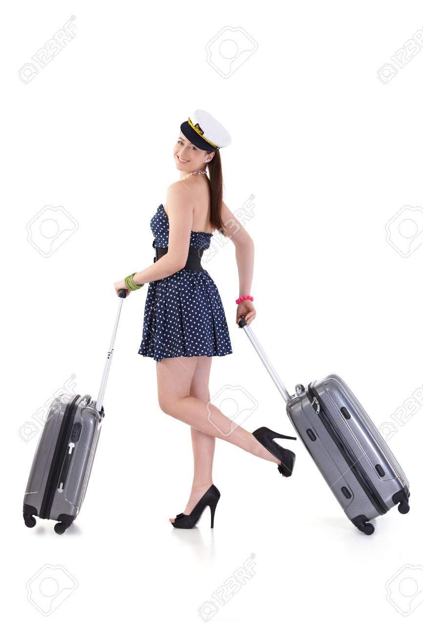 Young woman traveling to vacation with suitcase in summer dress, posing, looking at camera, smiling. Isolated on white. - 125785011