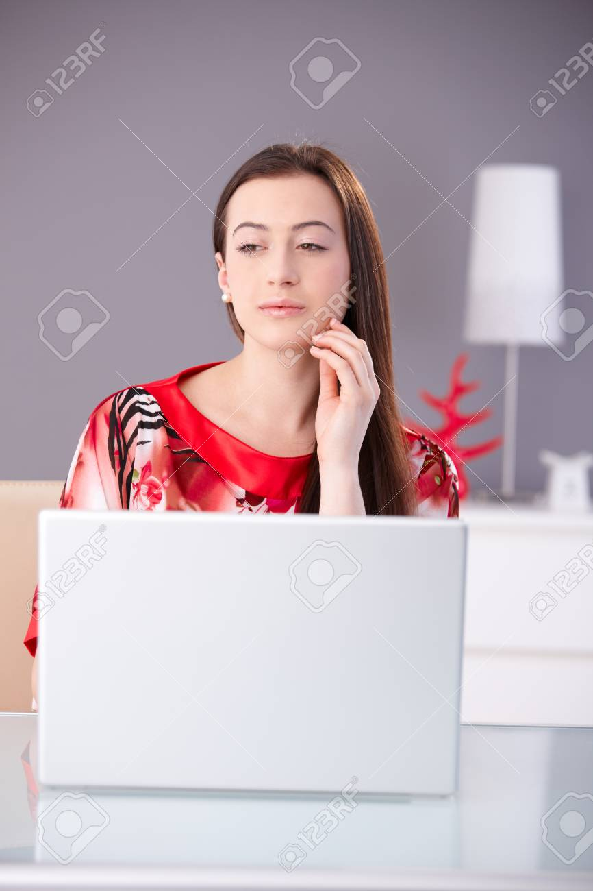 Beautiful young woman in red kimono working on laptop computer, looking away, thinking. - 125785018