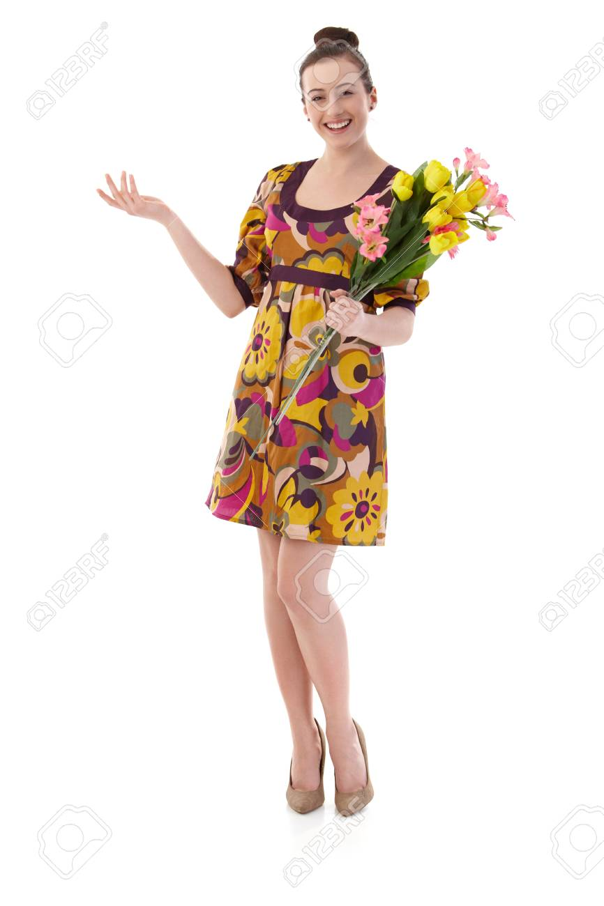 Happy young woman posing in summer dress, holding a bouquet of flowers, looking at camera, smiling. Isolated on white. - 125785021
