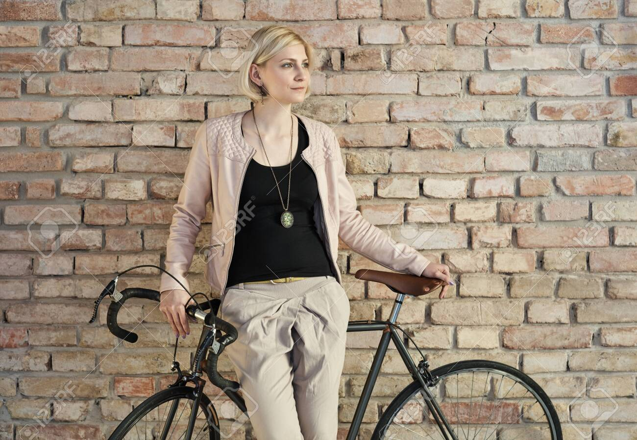 Stylish young woman leaning against bicycle front of brick wall. - 125784871