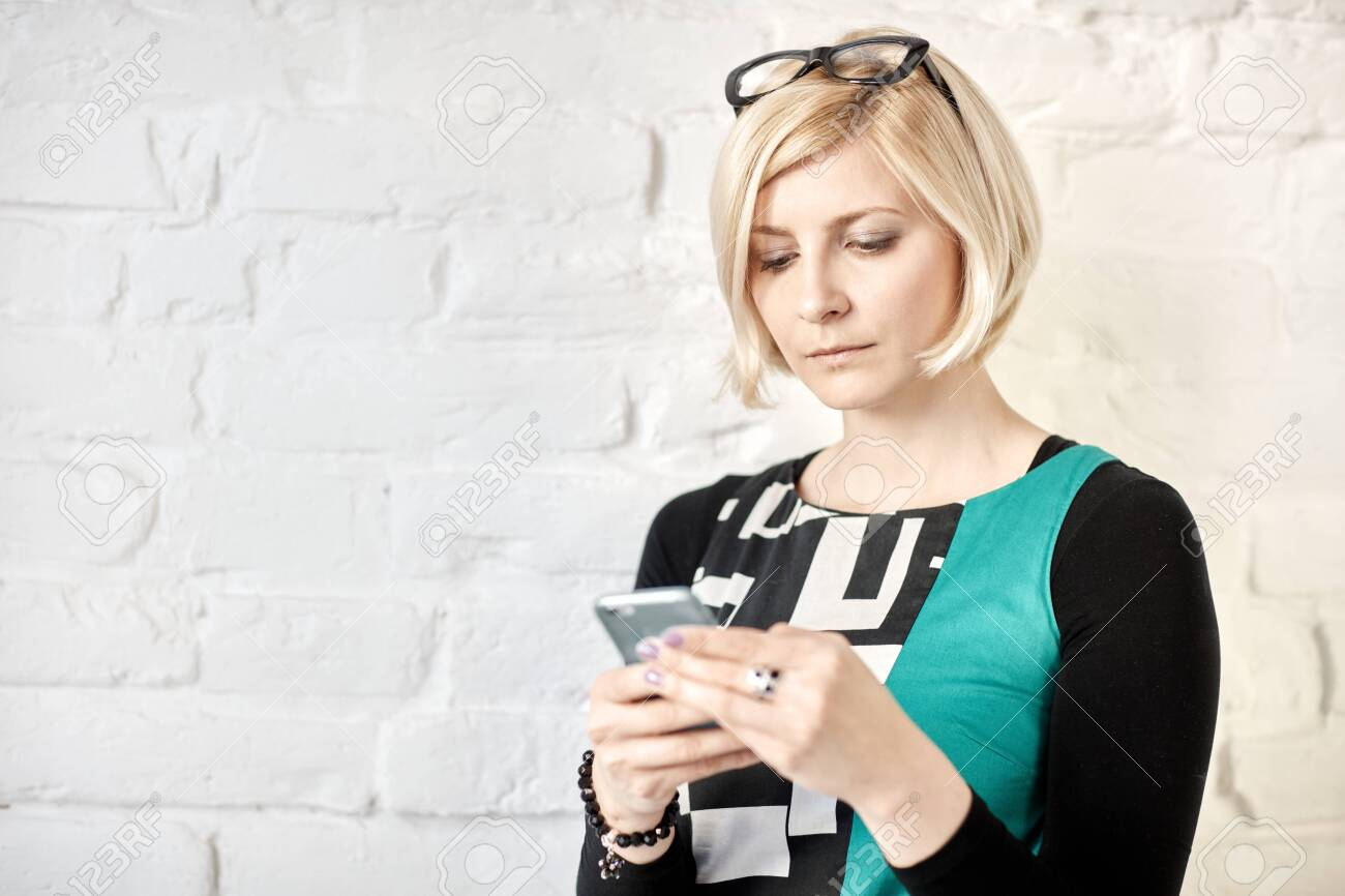 Young blonde woman using mobilephone. - 125784872