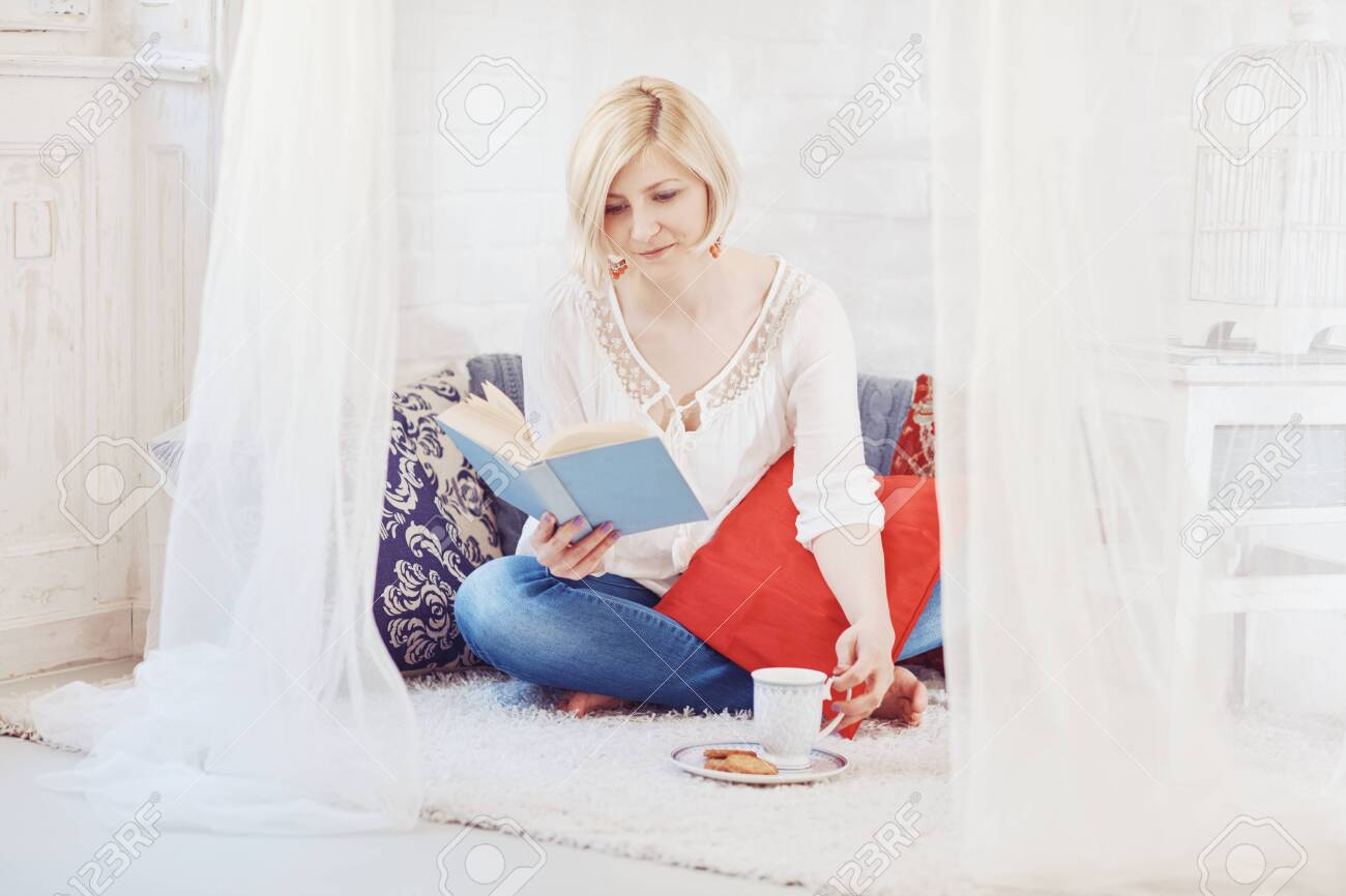 Blonde woman sitting at home on floor, drinking coffee, reading a book. - 125784873