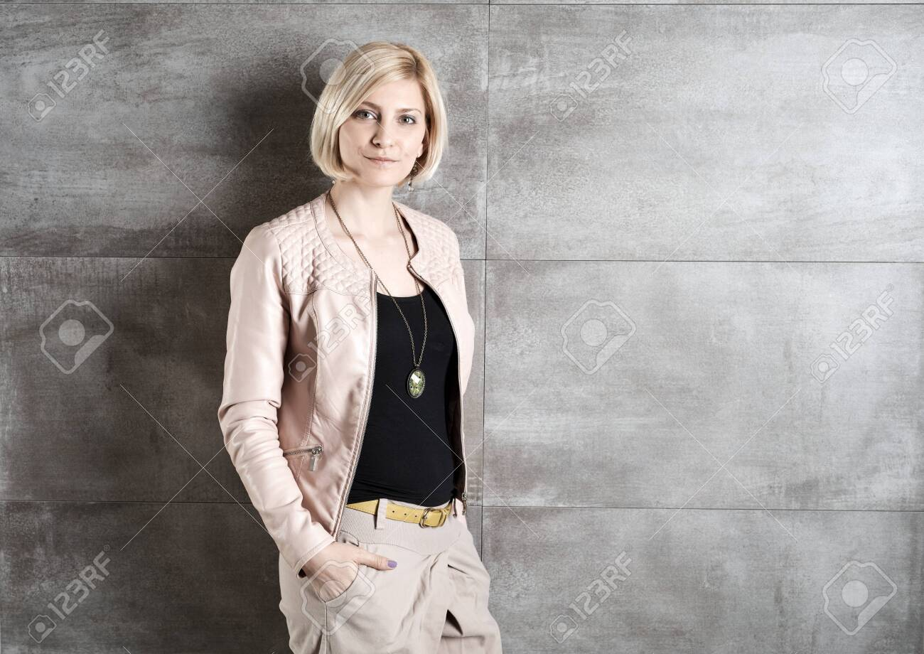 Stylish young woman standing against grey wall hands in pockets. - 125784782