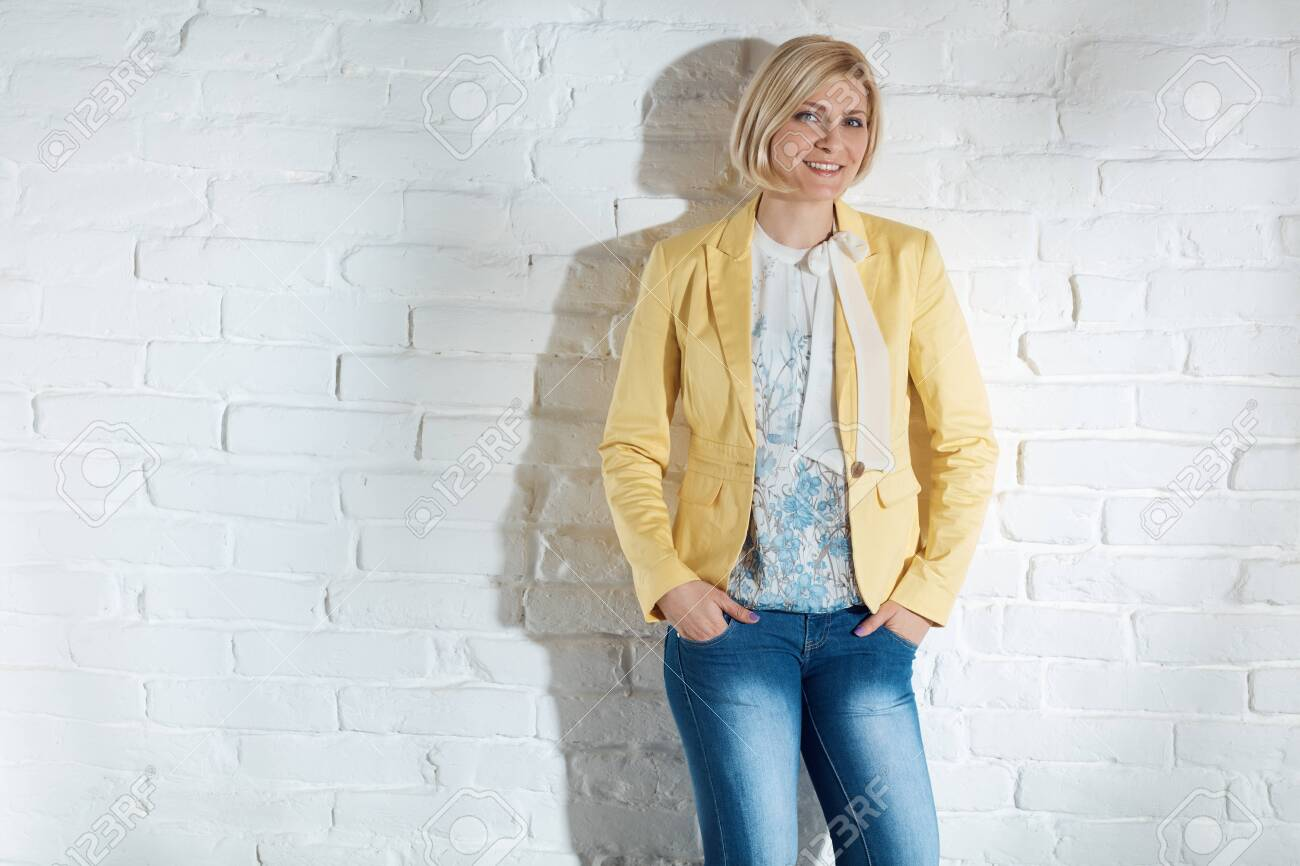 Casual young blonde woman standing by white brick wall with hands in pockets, smiling. - 125784451