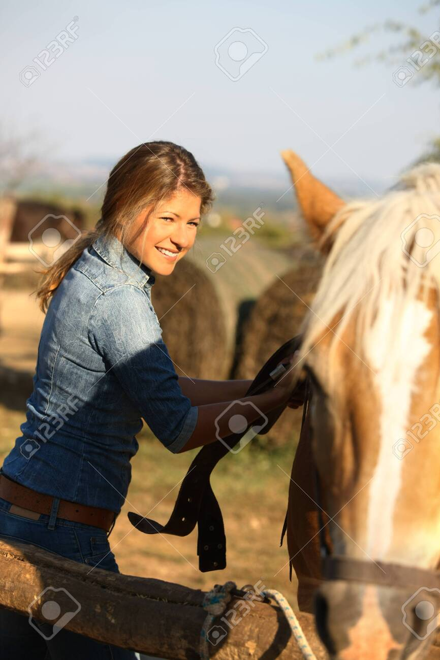 Happy young woman in jeans saddling a horse, smiling. - 130321156
