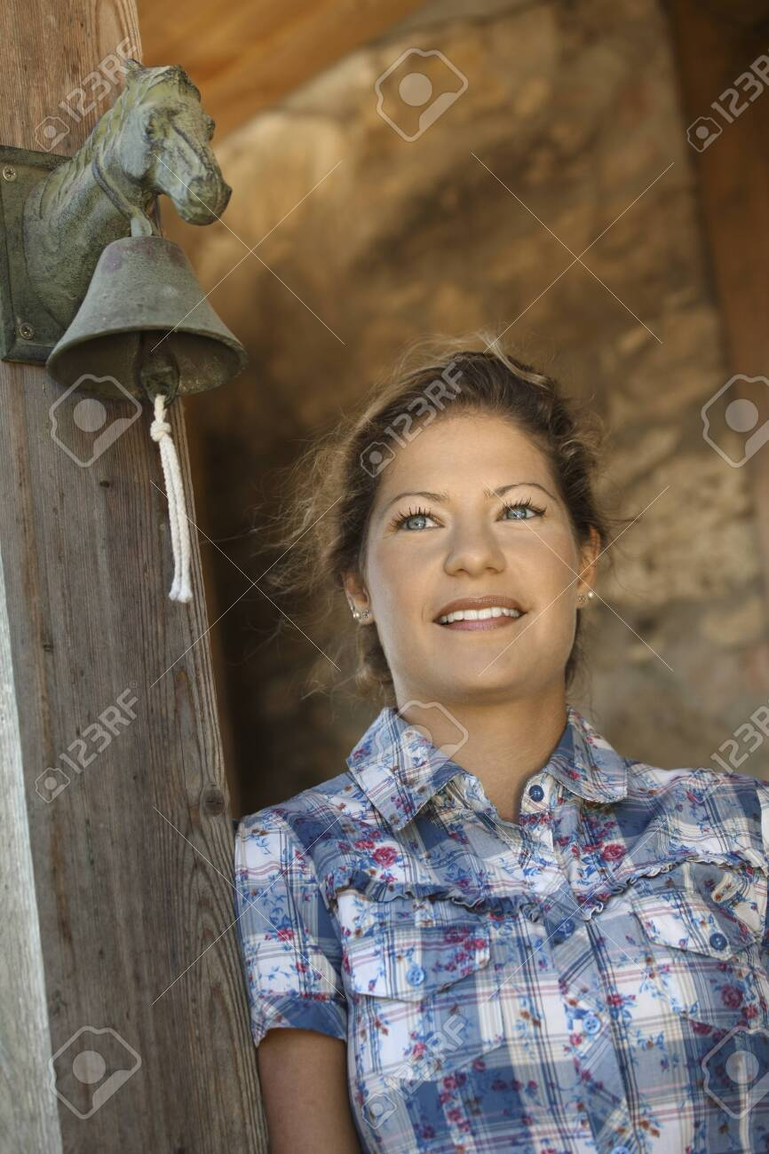 Portrait of young country girl standing in barn entrance, looking away, smiling. - 130321185
