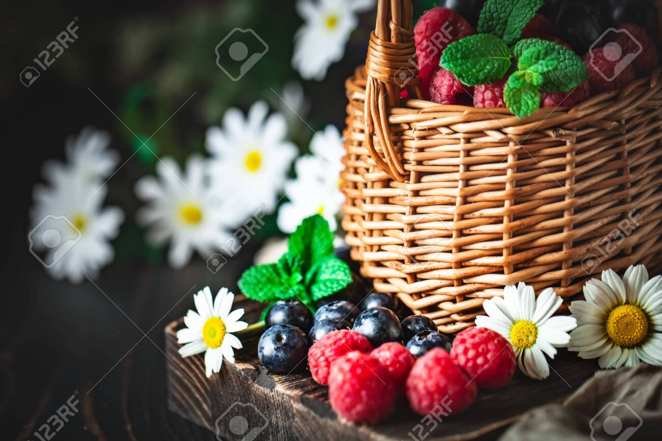 Raspberries and blueberries in a basket with chamomile and leaves on a dark background. Summer and healthy food concept. Selective focus. - 145285282