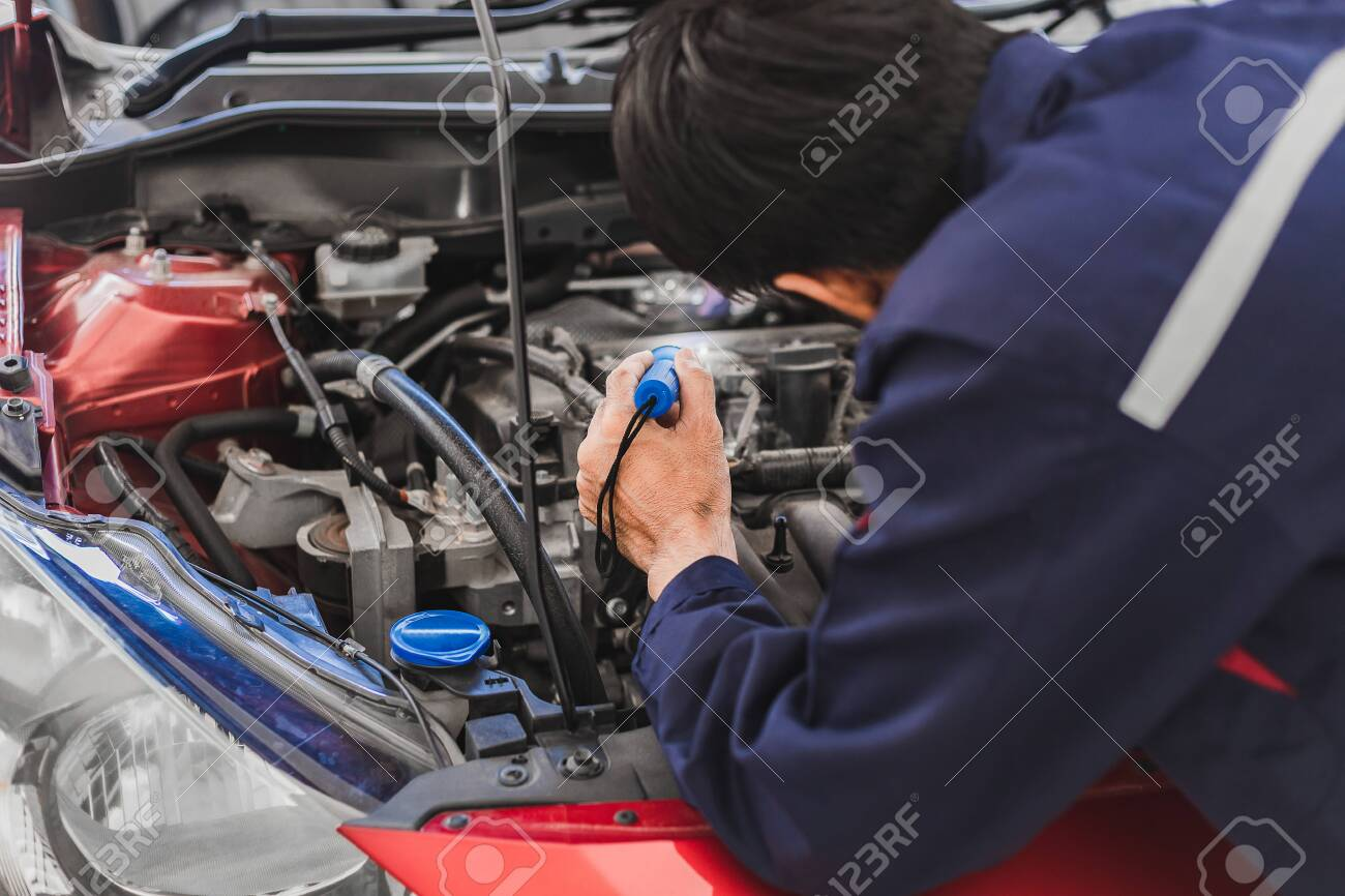 Asian Man mechanic inspection Shine a torch car engine checking bug in engine from application smartphone.Red car for service maintenance insurance with car engine.for transport automobile automotive - 150549432