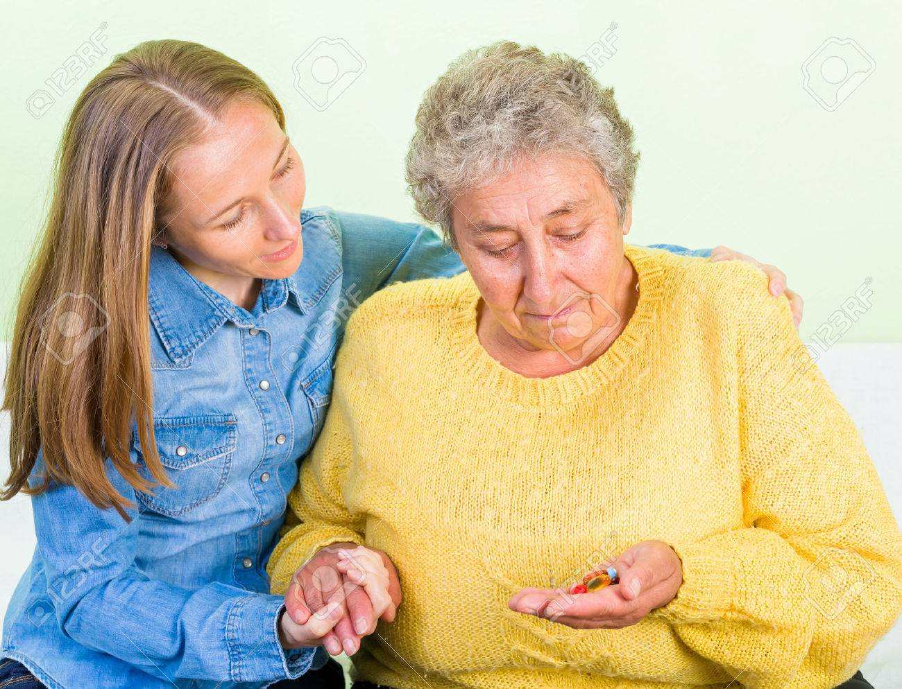 Young carer helping the elderly woman to take the pills Standard-Bild - 37013215
