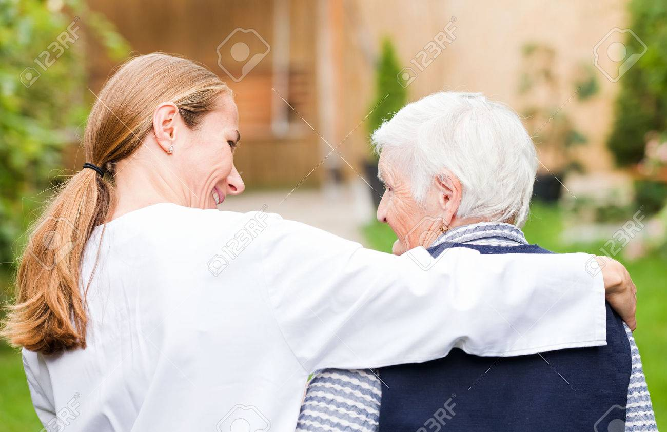 Young carer walking with the elderly woman in the park Standard-Bild - 38190568
