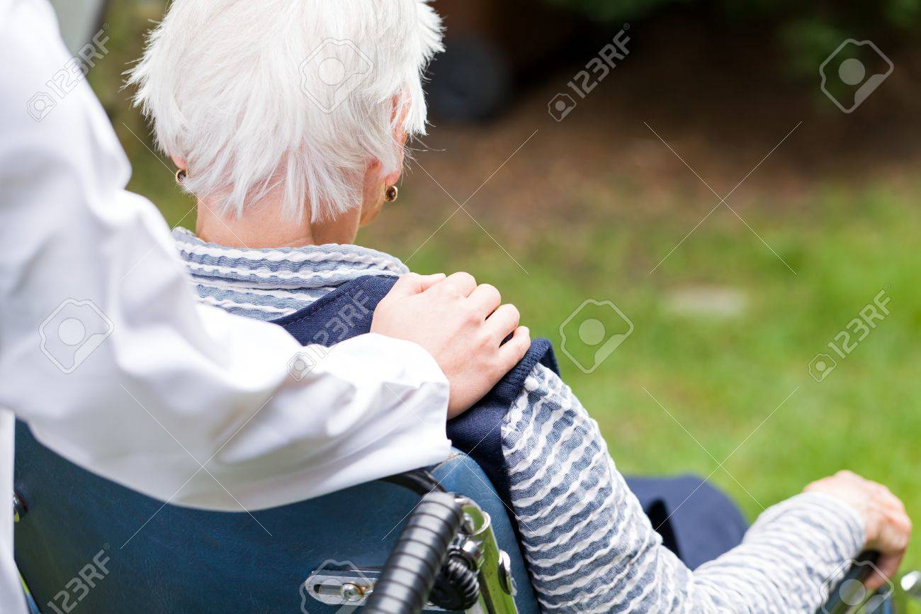Photo of young carer pushing the elderly woman in wheelchair Standard-Bild - 44593673