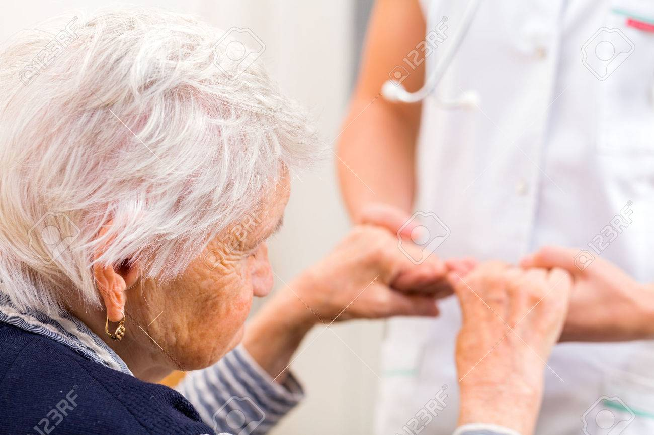 Young doctor giving helping hands for elderly woman Standard-Bild - 52956014