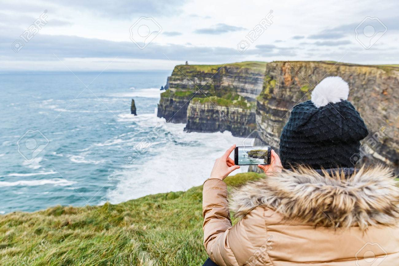 Tourist taking a photo with smartphone about Cliffs of Moher Standard-Bild - 52956158
