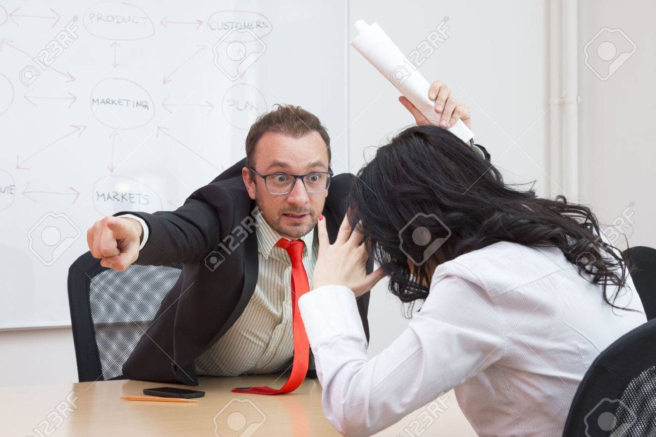 Angry boss firing female colleague by showing the door with his forefinger - 50705355