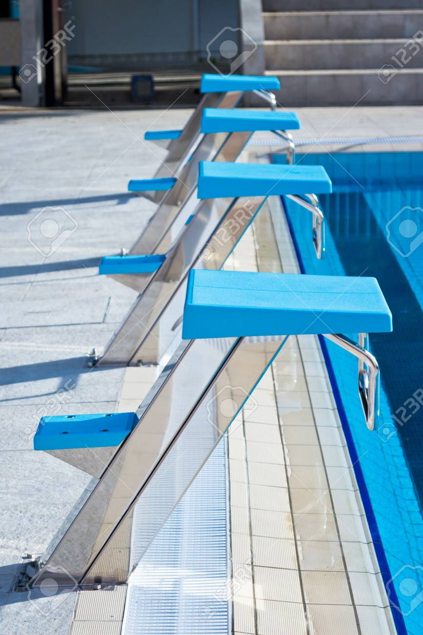 Starting blocks in a row at the edge of swimming pool outdoors...