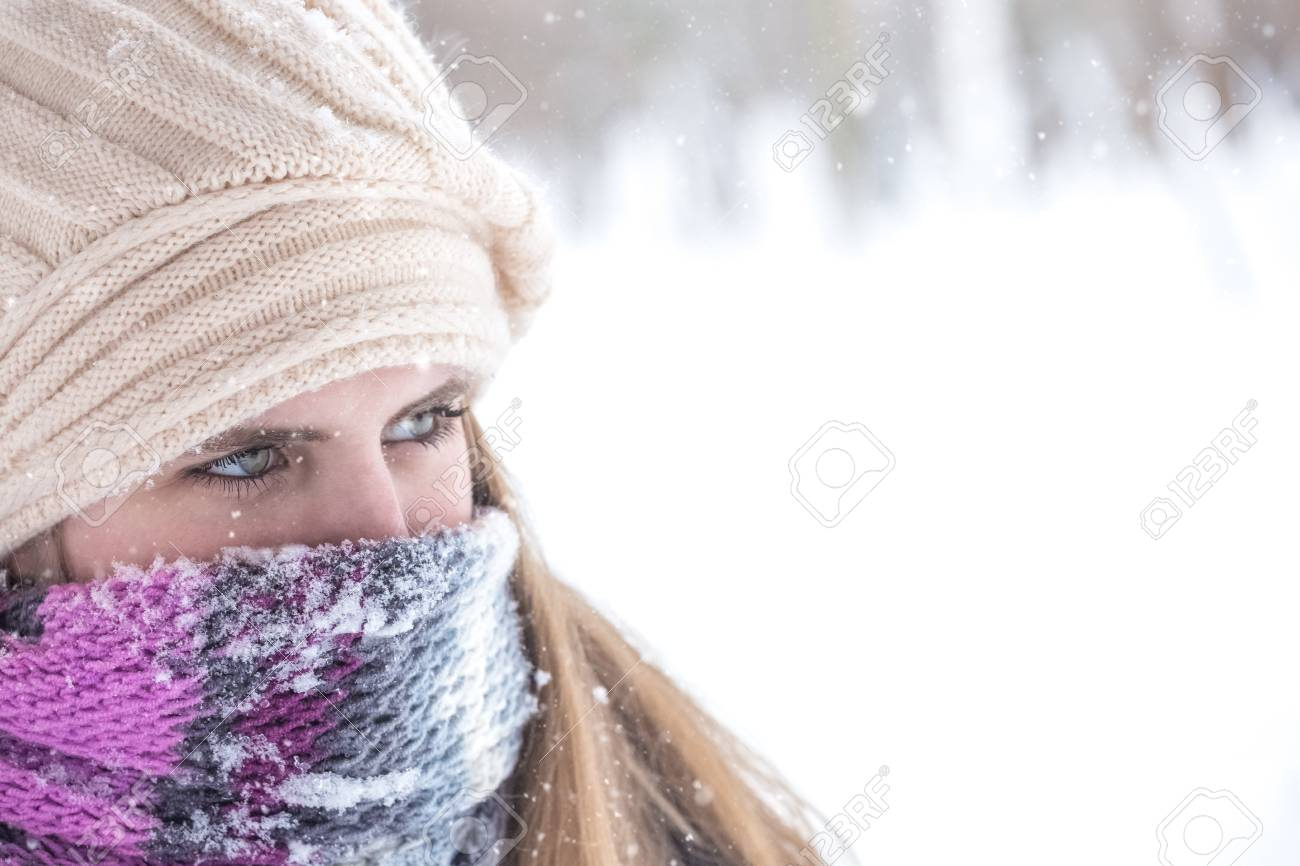 Portrait Of Young Woman With Face Covered From Cold On Winter Day